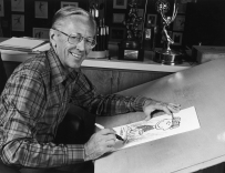 1978: Portrait of American cartoonist Charles M Schulz (1922 - 2001), creator of the 'Peanuts' comic strip, sitting at his studio drawing table with a picture of his character Charlie Brown and some awards behind him. Schulz created the comic strip in 1950. (Photo by CBS Photo Archive/Getty Images)