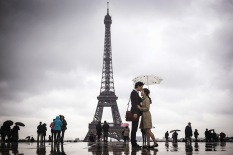 People gather on the Trocadero Square in front of the Eiffel Tower on a rainy day, on May 20, 2013, in Paris. AFP PHOTO / FRED DUFOURFRED DUFOUR/AFP/Getty Images